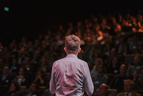 Un homme réalise une présentation devant un grand nombre de personnes