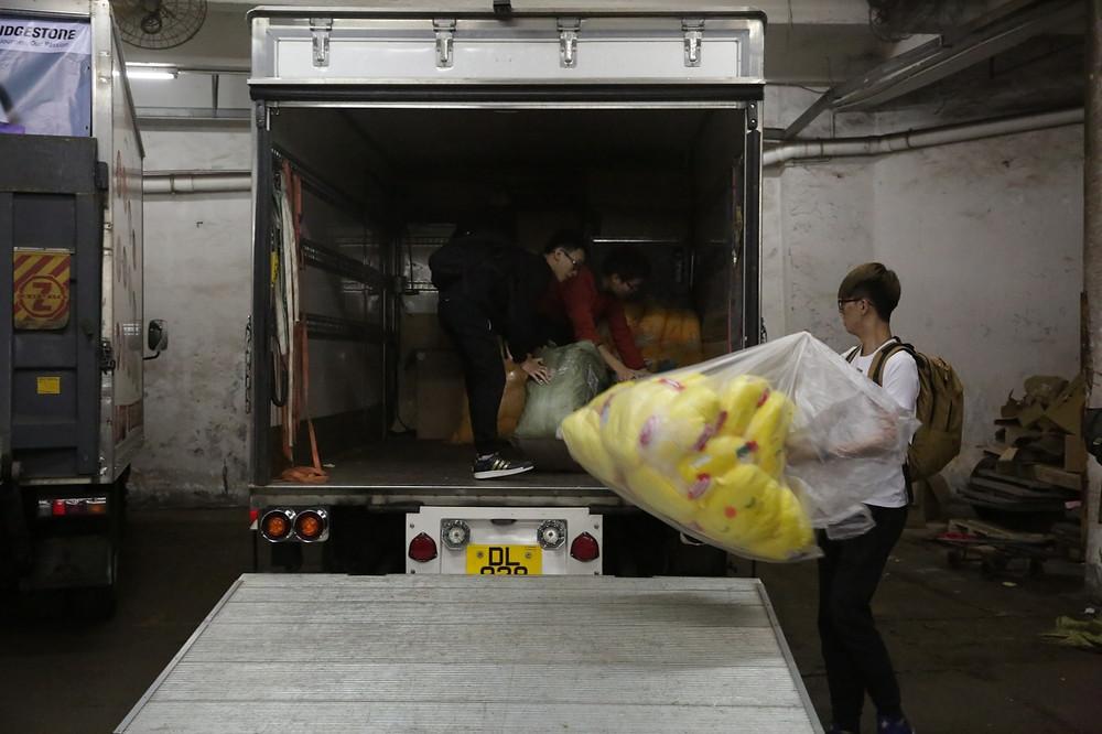 學生合力將產品運上貨車。(黃偉民攝)
