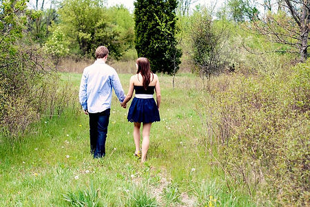 A couple walking on a grassy trail in the countryside, having a conversation