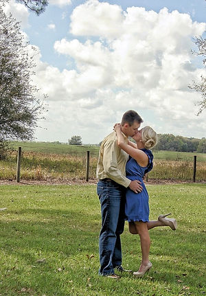 A couple standing and kissing in a grassy farm setting on a sunny day beneath a beautiful ice blue sky with puffy white clouds