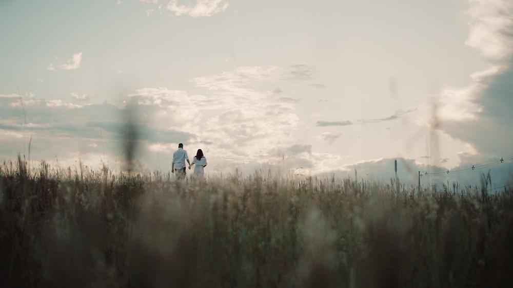 Casal caminhando no campo ao por do sol