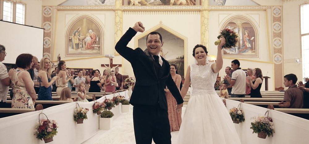 Recém casados saindo da igreja comemorando.