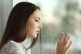 Sad Woman Looking Rain Through A Window.