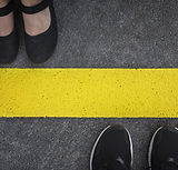 Legs of a couple standing opposite each other divided by the yellow asphalt line top view.