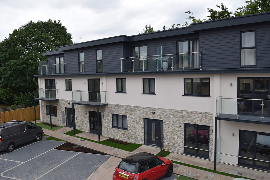 Admiral Windows and Conservatories Oxford home page photo of its own project of a multi apartment house in Witney with anthracite grey windows, doors, cladding, guttering and fascia