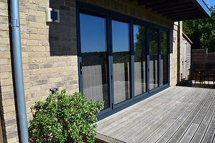 Anthracite Grey Aluminium Bi-fold five-section doors on decking