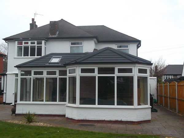 white uPVC conservatory with solid Equinox roof system in dark grey colour