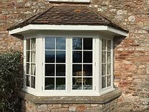 Four-section Bay window in cream colour and astragal bars
