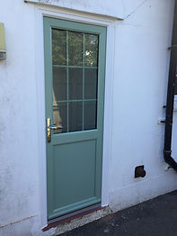 Chartwell Green uPVC back door with a top glass panel with astragal bars and smooth bottom panel