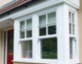 traditional white timber (wooden) sliding sash square bay window with sash horns