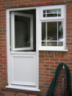 Conventional white upvc stable door with a top clear glass panel and a side window
