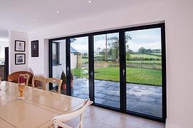 four-section aluminium bi-fold doors in black colour