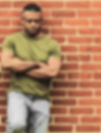 Fit man leaning against wall, in thought