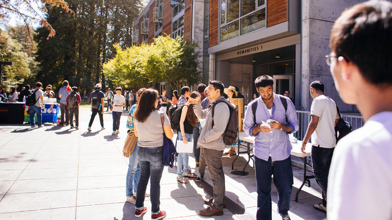 Groups of people talking outside of a building