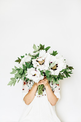 Young pretty woman hold white peony flowers bouquet on white background. Summer floral com