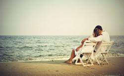 Romantic_Couple_Seating_on_Beach_Wallpaper_Download.jpg