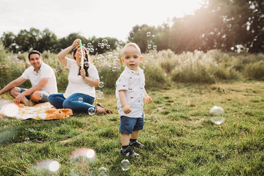 Family blowing bubbles in a long grass, Summer, Hertfordshire