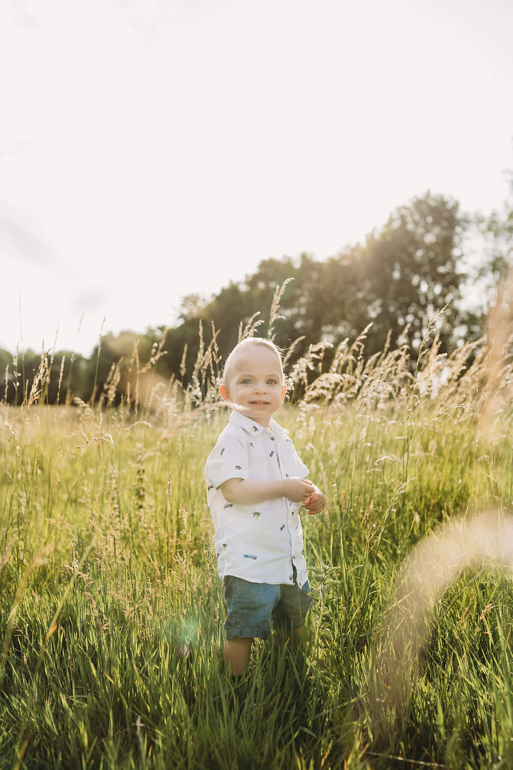 1 year old boy standing in long grass, Hertfordshire.
