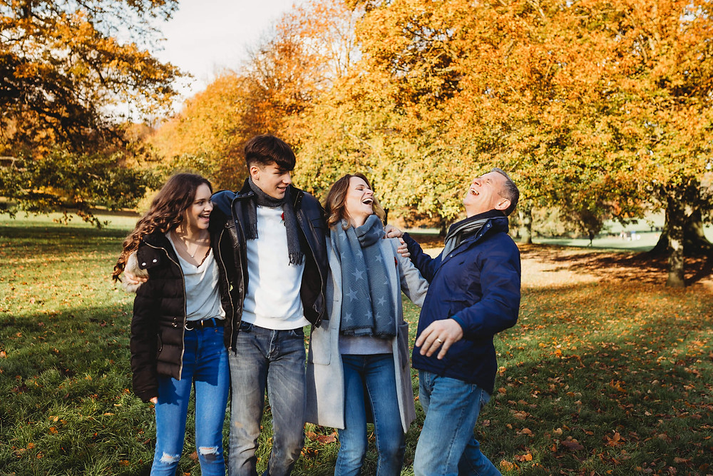 Family of four laughing in a park at Autumn, Hertfordshire