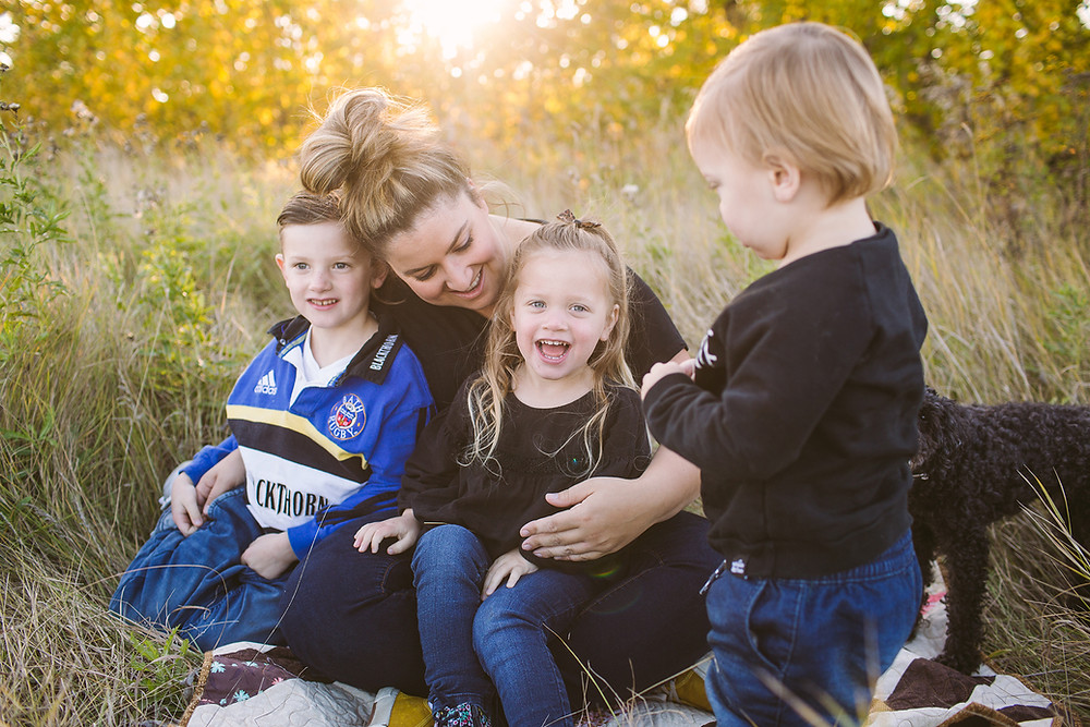Three children laughing with mom in fall field