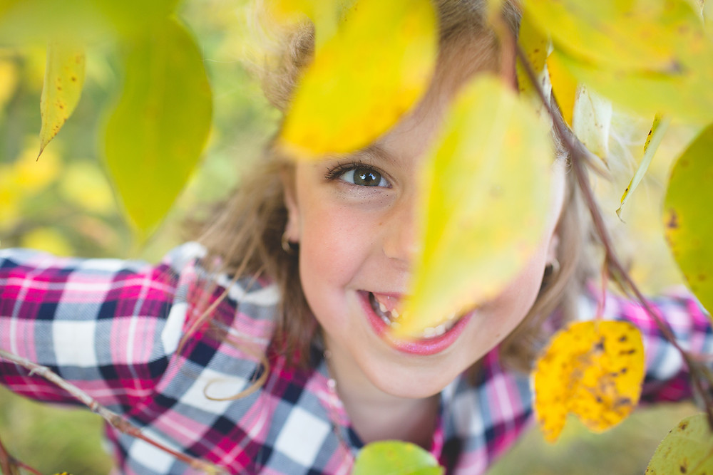 Little girl playing in yellow fall leaves
