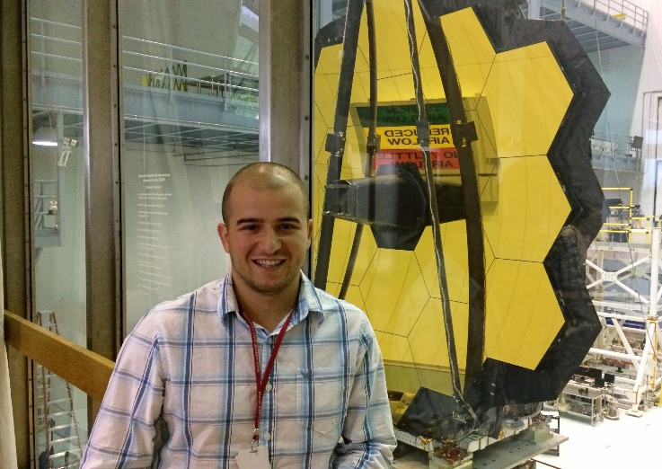 Andrei in front of the James Webb Space Telescope, on the observation deck of Goddard's High Bay Clean Room at NASA.