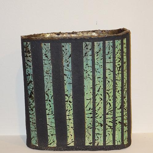Black chunky clay oval form with porcelain slip. Bronze glaze inside.