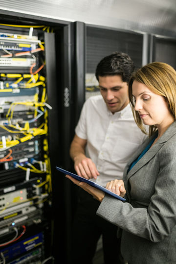 Man and Woman collaborating in front of a patch panel