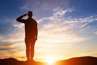 Soldier saltuting at sunset