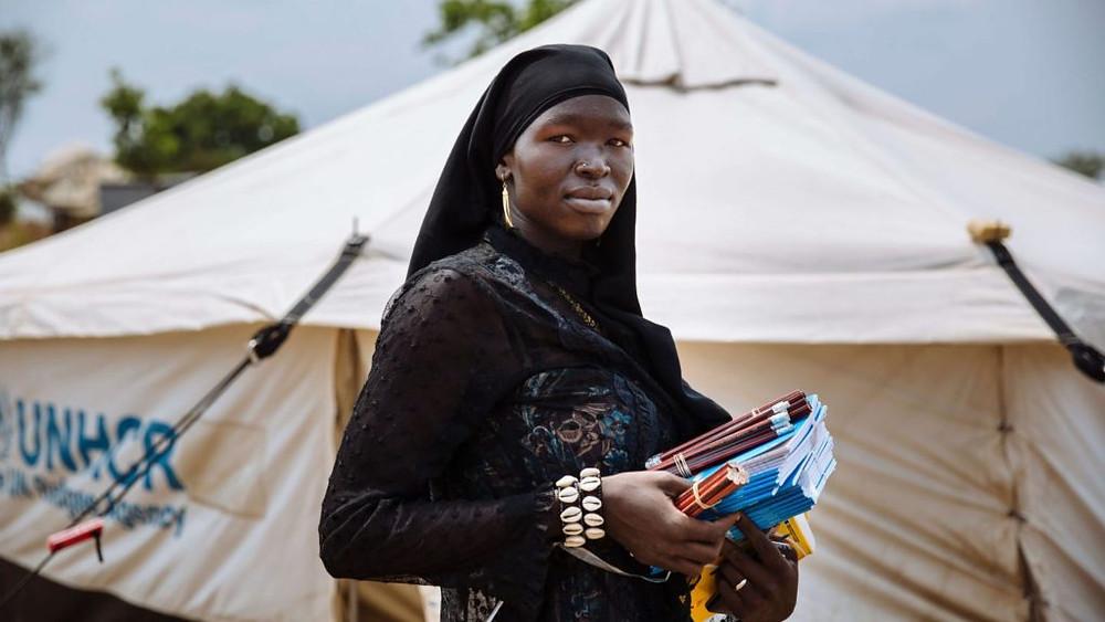 UGANDA/2017 — A professora Bako Zulaika mostra seus materiais de ensino do lado de fora de sua tenda, numa escola primária no campo de refugiados de Bidi Bidi. O centro de ensino era frequentado por mais de 48 mil crianças em março de 2017. Foto: ACNUR/David Azia