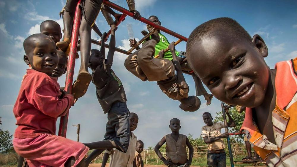 SUDÃO DO SUL/2014 — Um ano após a eclosão dos conflitos no Sudão do Sul, crianças sul-sudanesas refugiadas se divertem em um brinquedo instalado por uma organização parceira do ACNUR no centro de transição Nyumanzi, norte de Uganda. Foto: ACNUR/Frederic Noy