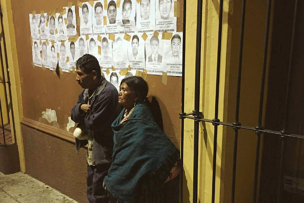 Pessoas em Oaxaca, no México, em frente a cartazes de desaparecidos. Foto: Jeca Taudte