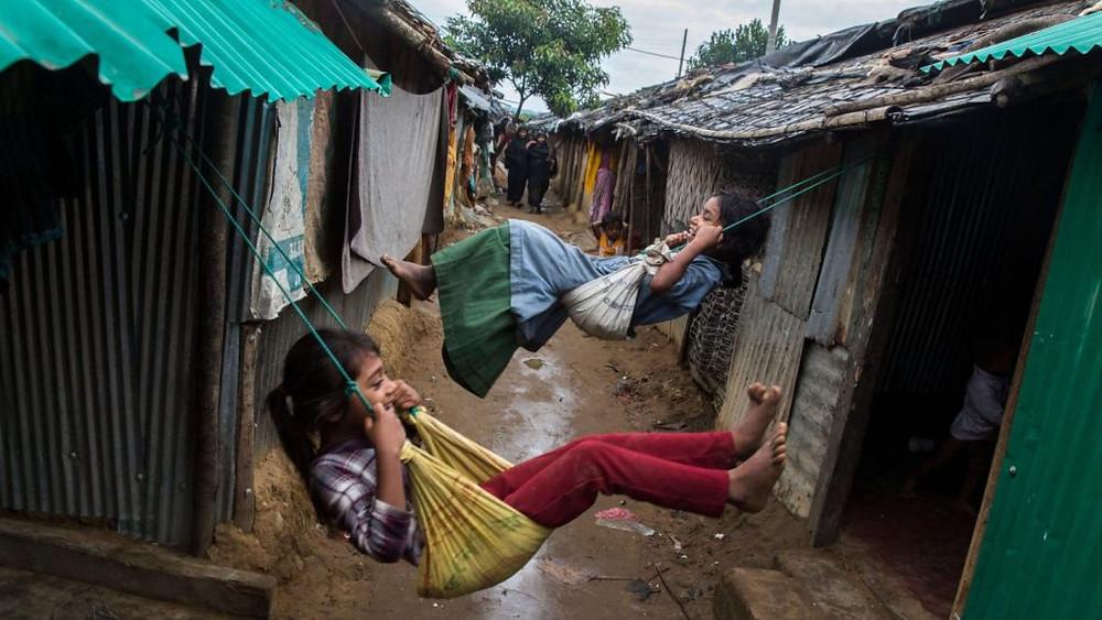 BANGLADESH/2017 — Noor, de oito anos, e Sameera, de dez, brincam em balanços no campo de Kutupalong. O local abriga refugiados rohingya que fugiram para Mianmar em 1991, buscando proteção. Muitas crianças nasceram no campo e não conhecem outra realidade. Foto: ACNUR/Andrew McConnell