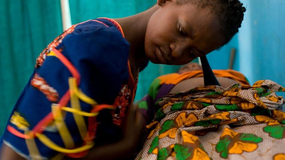 """TANZÂNIA/2008 — A filha de refugiados burundineses, Janet Ogeste, nasceu na Tanzânia em 1978. Três décadas depois, ela trabalhava como parteira no vilarejo de Lukama. """"Quando ajudo a trazer outro humano para o mundo, sinto-me muito feliz"""". Foto: ACNUR/Brendan Bannon"""