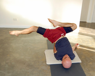 The interflora variation of sideways shoulderstand, just before stepping down into a sideways version of bridge pose.