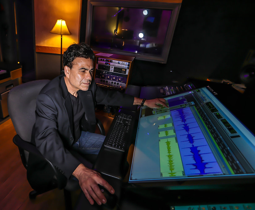 Music producer using technical recording equipment to enhance a recording.
