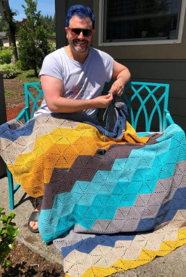 "Mathew Boudreaux works on an afghan during quarantine. He has used this time at home to complete things that he had never had time to get to. ""It was a way not to have to think,"" he says. ""I didn't want to come up with new projects."" (Helena Boudreaux)"