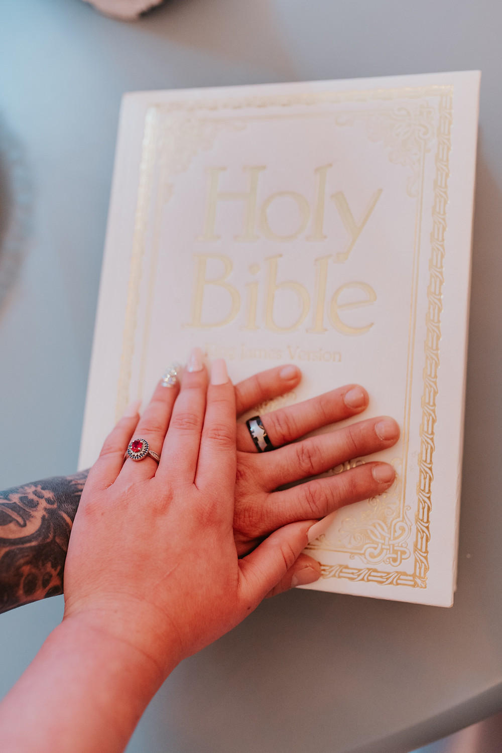 man and woman with their hands placed on the bible