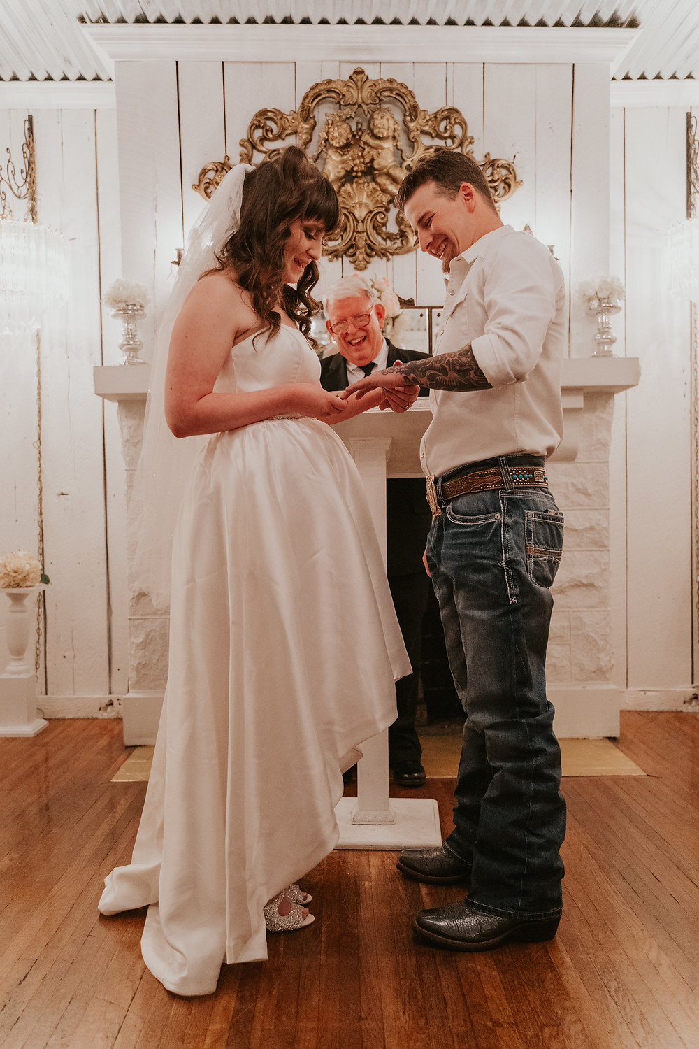 woman putting on her husband's wedding band at the altar