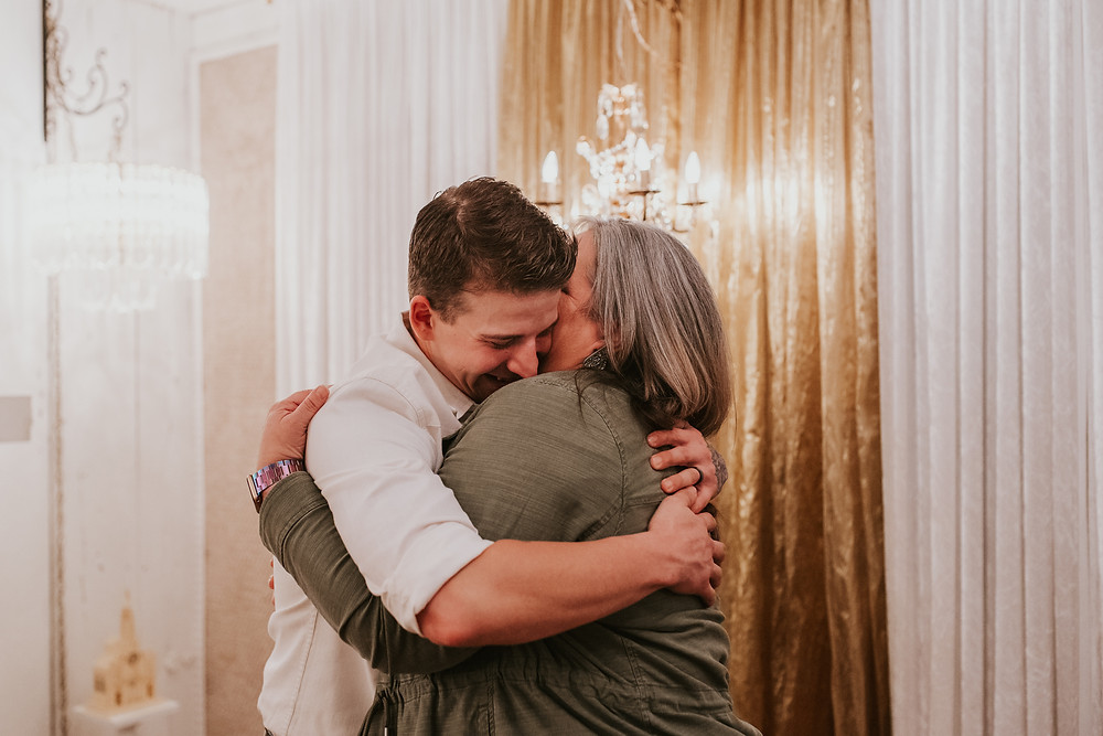 mother hugging her son on his wedding day with smiles on both of their faces