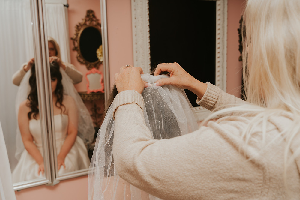 mom helping bride put on her veil