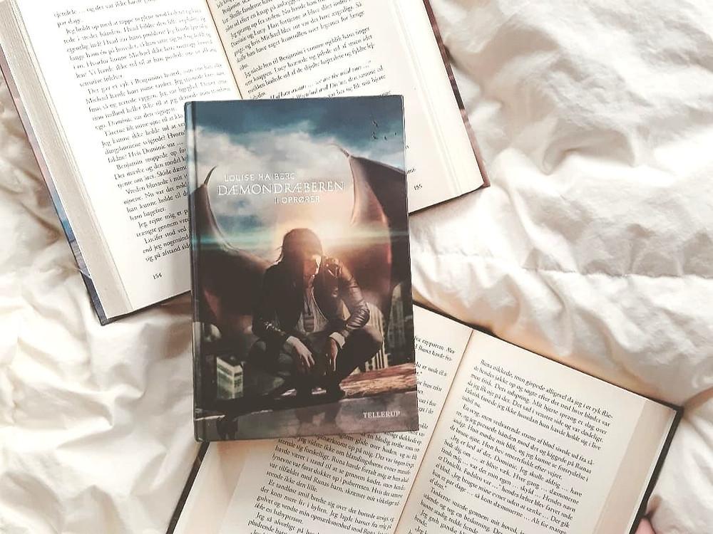 To åbne bøger med Dæmondræberen 1 liggende på sig.