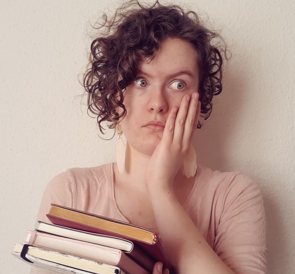 Billede af Mie Hald med favnen fuld af notesbøger og et bekymret ansigtsudtryk.
