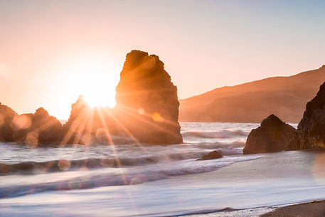Rays of sunrise beaming through a rock formation in the surf.