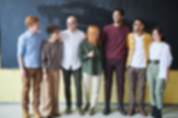 group-of-people-standing-beside-chalk-bo