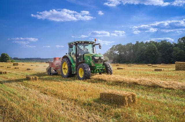 Traktor mit Anhänger auf Feld bei blauem Himmel