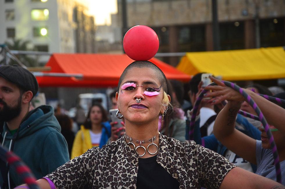 Uma pessoa equilibra uma bola vermelha na cabeça careca. Ela tem cílios postiços cor-de-rosa, maquiagem, vários piercings e uma camisa com estampa de oncinha.