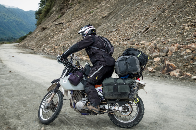 Kelvin standing with his tank bag - photo by Michnus Olivier of PikiPikioverland.com