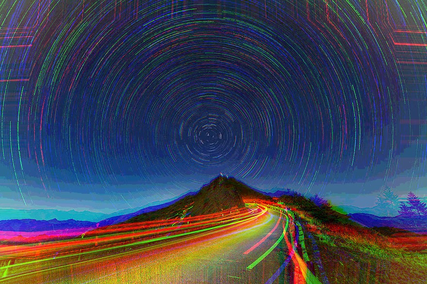 Highway through the mountains to the stars at night
