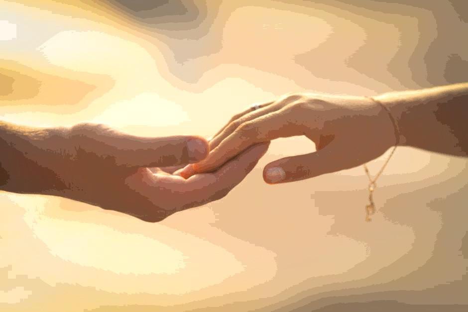 Man's hand holding woman's hand
